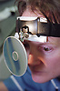 Portrait of staff nurse in aural care centre using head mirror to examine patient's ear,