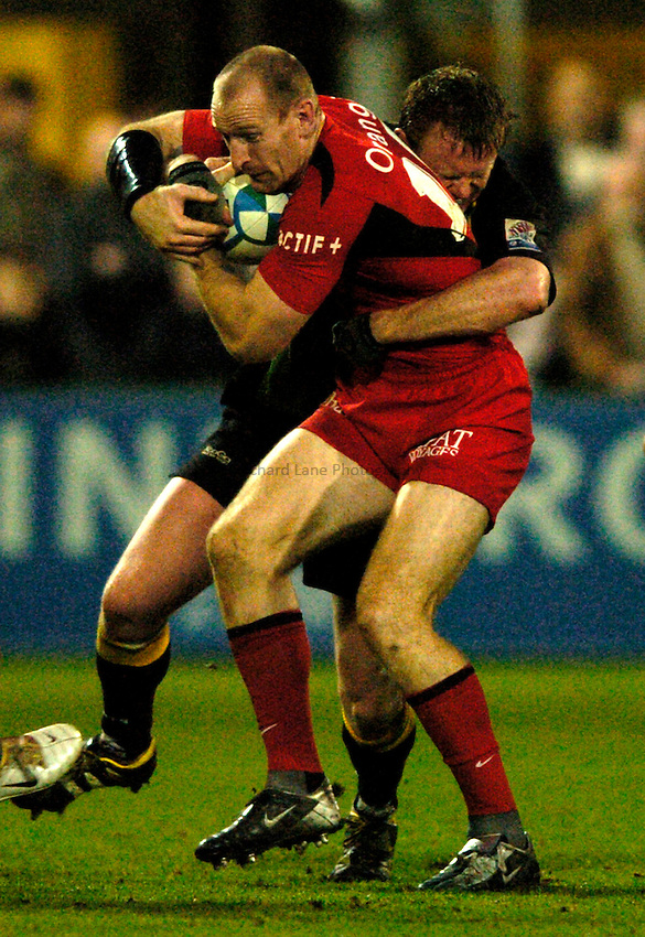 Photo: Richard Lane..Northampton Saints v Toulouse. Heineken Cup. 04/12/2004..Gareth Thomas is tackled by Mark Soden.