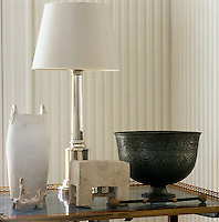 A table lamp with a silver base stands amongst a collection of artefacts against the backdrop of a three-dimensional striped plaster wall