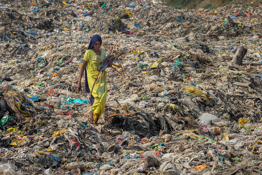 A woman collectes recyclables on the Guwahati rubbish tip India
