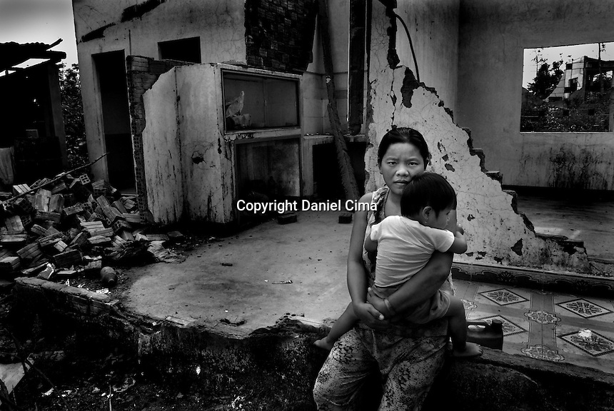 Portrait of a mother and daughter   (typhoon survivor) at home in .Da-Nang, The Socialist Republic of Vietnam. May 2007