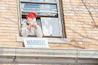 A woman looks out her window as Democratic presidential candidate and Massachusetts senator Elizabeth Warren and husband Bruce Mann greet supporters gathered along Linnaean Street as she walked to Graham & Parks School to vote in the Massachusetts primary as part of Super Tuesday voting in Cambridge, Massachusetts, on Tue., March 3, 2020. The polling place is just a few blocks from Warren's residence. Polls show Warren and Vermont senator Bernie Sanders in a near tie in the Massachusetts Democratic party primary.