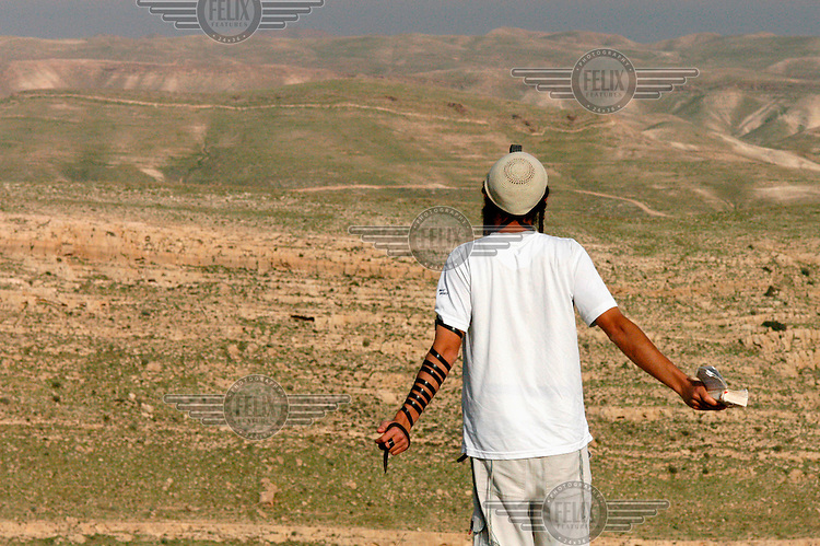 A Jewish settler conducts his midday prayers while facing east towards the Judean desert, in the West bank illegal Jewish outpost of Tekoa D.  The outpost is one of several due to be removed when the Israeli government implements the 'Road Map'.