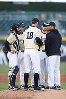 Wake Forest Demon Deacons assistant coach Matt Hobbs (right) has a meeting on the mound with starting pitcher Carter Bach (18), catcher Logan Harvey (left), Johnny Aiello (2), and Jake Mueller (6) during the game against the Charlotte 49ers at BB&T BallPark on March 13, 2018 in Charlotte, North Carolina.  The 49ers defeated the Demon Deacons 13-1.  (Brian Westerholt/Four Seam Images)