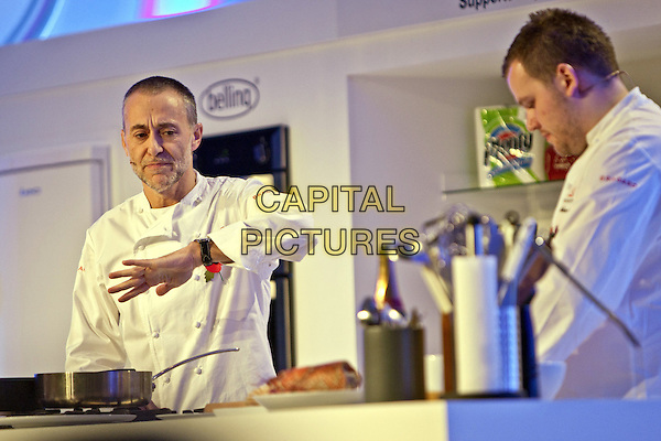 Michel Roux Jr.BBC Good Food Show London 2012, Olympia, Kensington, London, England..November 10th 2012.half length white chef jacket hand arm cook cooking poppy stubble beard facial hair  .CAP/MM/PP.©Mike Mustard/PP/Capital Pictures