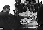 Rev. Ralph Abernathy scatters flowers over the casket of Martin Luther King Jr during burial rites at cemetery in Atlanta Georgia on April 9, 1968. (Photo copyright Jim Peppler 1968).