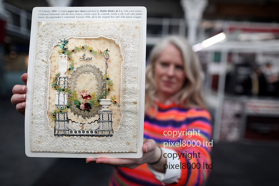 Pic shows: 1840 valentine card - lace, silk and gold leaf of greek urns and cupid<br /> <br /> Valentine's Cards  through the ages<br /> collection at an Exhibition in London today  13.2.19<br /> <br /> A selection of the world's oldest Valentine's Day cards are on display until 16th February at Stampex International, the UK's largest stamp collecting exhibition, at the Business Design Centre, Islington. Collected by Judith Holder over the last 50 years, some date back as far as 1720.<br /> <br /> <br /> Cards being held by Susan Wylie who is overseeing the exhibition <br /> <br /> <br /> <br /> <br /> pic by Gavin Rodgers/Pixel8000