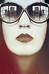 Vintage close-up portrait of a young woman with pale skin and big vintage glasses and red lipstick staring at the camera.