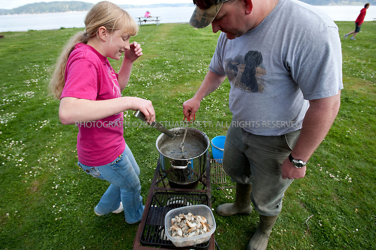 4/25/2009--Skokomish Nation, WA, USA..Bob Haney (right) and his daughter Sara, cook clams they have collected at the Potlatch State Park on  the Hood Canal. The Hood Canal is a glitteringly beautiful 60-mile long fjord and the western waterway of Puget Sound, located about an hour and a half outside Seattle. With the snow-clad Olympic Mountains as a backdrop and beaches bristling with oysters, clams, mussels, and crabs, it's ripe for a shellfish safari...©2009 Stuart Isett. All rights reserved.