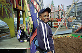 A boy plays on a rope swing at Hornimans Adventure Playground, North Kensington, London.