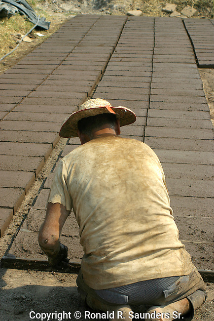 Poor Mexican man labors to create a brick platform<br />