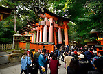 Tourists entering Senbon Torii path leading to inner shrines of Fushimi Inari Taisha head shrine in Fushimi Ward, Kyoto, Japan 2017