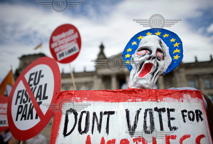 A mask in the form of Edvard Munch's The Scream is held up surrounded by a halo in the form of the European flag aling with other posters at a demonstration against the EU fiscal pact outside the Reichstag in Berlin. Bundestag members are set to vote on ratification of the fiscal pact and the ESM (European Stability Mechanism) inside the parliament. Left wing party Die Linke are past of the protest.