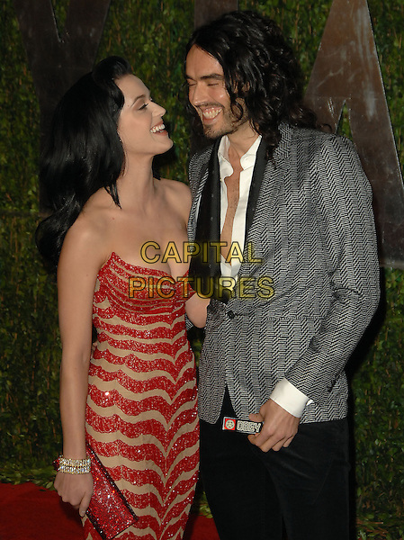 KATY PERRY & RUSSELL BRAND.The 2010 Vanity Fair Oscar Party held at The Sunset Tower Hotel in West Hollywood, California, USA..March 7th, 2010.oscars half length dress  red beige strapless striped stripes zig zag pattern clutch bag grey gray suit jacket coupe stubble facial hair smiling profile.CAP/RKE/DVS.©DVS/RockinExposures/Capital Pictures.