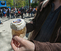 """Happy hockey fans and other visitors get free promotional cupcakes in Madison Square Park in New York at the kick-off of the partnership between the NHL and Crumbs Bake Shop on Tuesday, April 30, 2013. Crumbs Bake Shop will be selling National Hockey League """"Stanley Cupcakes"""" with the NHL and team specific logos. The promotional campaign, with the NBC Sports Group also in the partnership, leads up to the 2013 Stanley Cup Playoffs. (© Richard B. Levine)"""