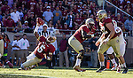 FSU quarterback Jameis Winston (5) passes as he slips down on a perfect football fall afternoon when the Florida State Seminoles defeated the North Carolina State Wolfpack 49-17 in their NCAA football game  in Tallahassee, Florida.