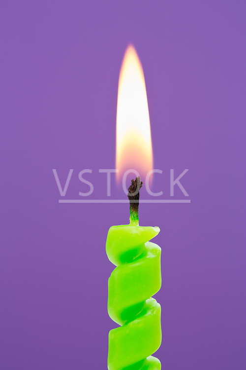 Burning candle on purple background