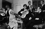 """October 28th, 1966. Hotel Waldorf Astoria, Manhattan, NYC. In the room of Maurice Chevalier after his performance at the Show """"April in Paris"""". On the picure we can see: Jose Reyes singing, at the guitar Manitas de Plata, Charles Aznavour, Marcel Amont and sisters Alice and Ellen Kessler."""