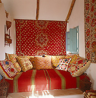 A daybed in this bright corner of the pool/guest house is surrounded by red textiles and covered in an array of beautiful patterned cushions