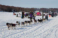 Bob Bundtzen and team runs by spectators on the trail on Long Lake during the restart of the Iditarod at Willow on Sunday, March 3, 2013.