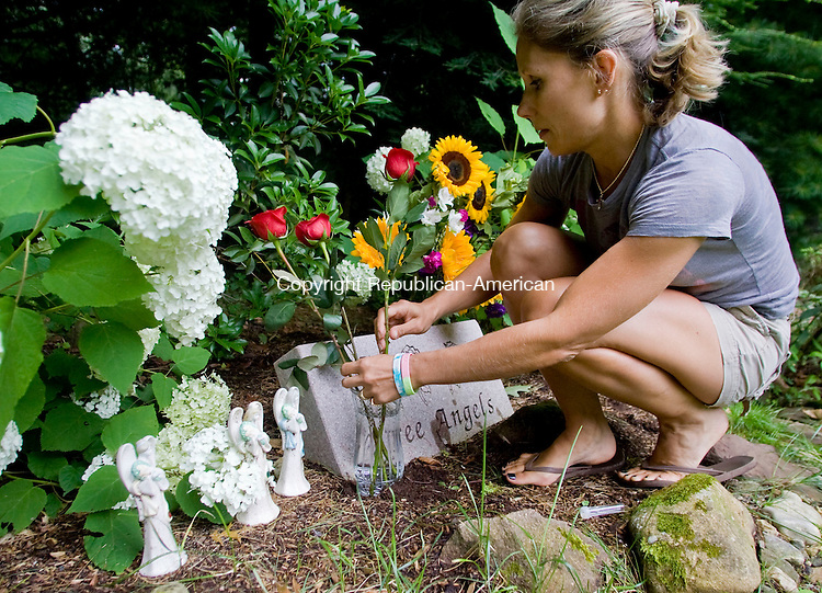CHESHIRE, CT - 23 JULY 2009 -072309JT04-<br /> Kim Ferraiolo, next door neighbor of the Petit Memorial Garden on Sorghum Mill Drive in Cheshire, sets up roses in front of three angel figurines and a statue that reads &quot;three angels&quot; that were left at the garden on Thursday, the two-year anniversary of the murder of Jennifer Hawke-Petit and her two daughters Hayley and Michaela during a home invasion at the site. The house where the murders occurred, which has since been demolished, stood at the site where the garden is planted.<br /> Josalee Thrift Republican-American