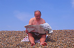 AYBT24 Middle aged man reading Times newspaper sport and business in swimming costume on beach