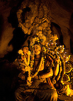 sculpture of Devi (most likely shakti of Shiva) in gloomy yellow light   in sancutary of   Batu Caves, Kuala Lumpur, Malaysia, 2012. Thaipusam ceremonies, celebrated by tamile Hindu community in Malaysia, take place  in Sanctuary of Batu Caves at the border of Kuala Lumpur, each year around end of January or beginning of February, according to Hindu moon calendar. The event is paying hommage to Lord Murugan, a spirit or god created by Shiva to lead the army of gods against the army of evil demons, finally defeating the evil spirits. There are many ways to present offerings or sacrifices for this major religious event. Devotees mortify their bodies by carrying heavy kavaris with spears fixed in their skin or fruits, flowers and little post with holy milk fixed with hooks in their skin, ascending the stairways to the sanctuary in trance, `followed by assistant  taking care and musicians playing loud and fast rhythmic trance music.  Many families shave their head in a ritual before ascending the stairways, as part of rituals to obtain salvation for their ancestors.