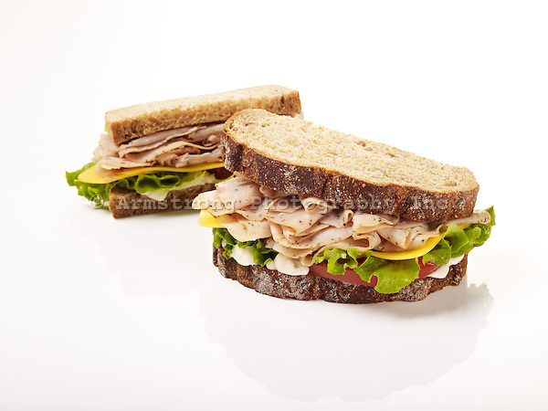 Two turkey sandwiches on whole wheat bread, on a white background