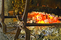 The fire place with cast iron things to put the logs on waning fire and perfect coals for grilling, a burning log Truffiere de la Bergerie (Truffière) truffles farm Ste Foy de Longas Dordogne France