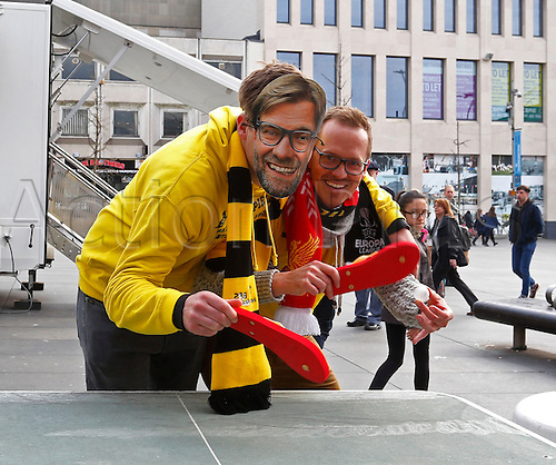 14.04.2016. Liverpool, England.  Borussia Dortmund fans, one wearing a Juergen Klopp mask play table tennis with flipflop shoes in Liverpool city centre ahead of tonight's UEFA Europa League quarter finals  match between Liverpool FC and Borussia Dortmund at the Anfield stadium in Liverpool, north west Britain 14 April 2016.