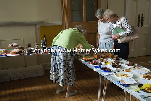 Petersham village fete Produce and Flower Show Richmond, Surrey UK. Middle class England senior women checking out cake baking entries.