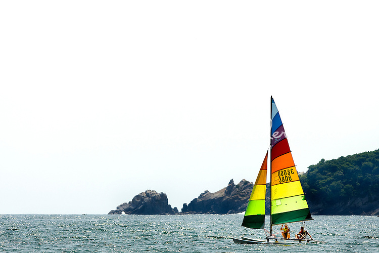 A boat with colorful sail floats in the gentle waves of Zihuatanejo Bay near Playa la Ropa Beach in Zihuatanejo, Mexico.  (taken August 2007). Photo by Patrick Schneider Photo.com