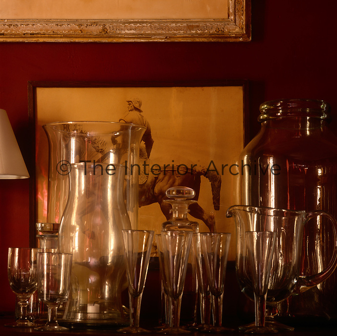 Wine glasses, hurricane lamps and jars are displayed on a shelf against a red wall.