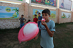 A Palestinian boy eats candy cotton as he plays at a park in Gaza city on August 18, 2019. Fayiz al-Wakeel, or 'the smile maker', developed his own candy floss machin to work by battery power to help him moving between vital districts in the Gaza city and make cotton candy with lovely shapes. Photo by Mahmoud Ajjour