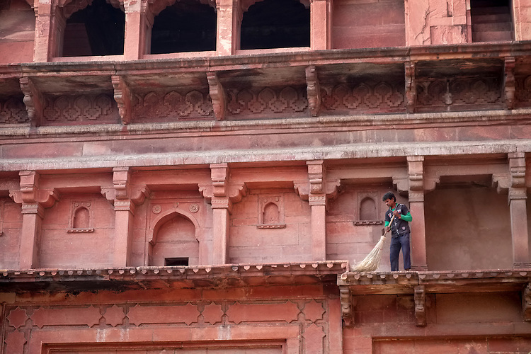 A sweeper attends to the ledges on the multi-level exteriors of Agra's Red Fort.