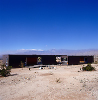A prefabricated modern house set within its desert landscape
