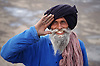 Portrait of elderly man with full grey beard smiling and saluting,