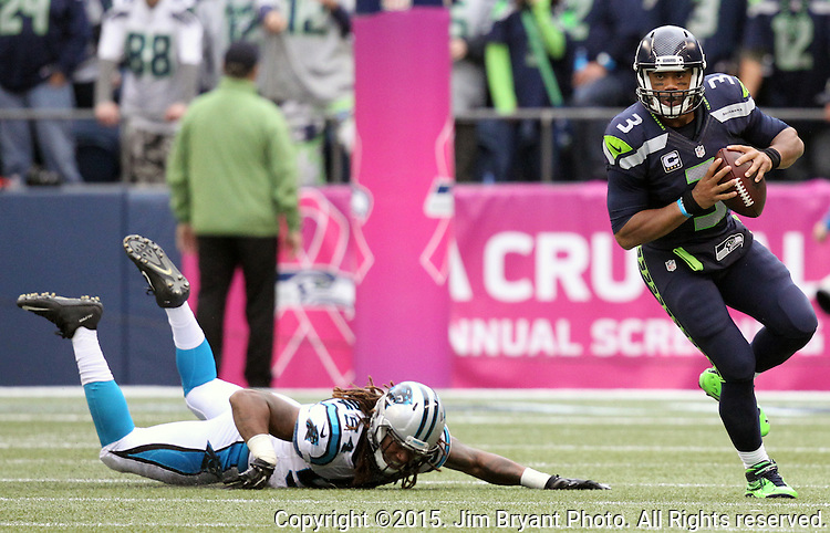 Seattle Seahawks quarterback Russell Wilson scrabbles away from against Carolina Panthers linebacker Shaq Thompson (54)  at CenturyLink Field in Seattle on October 18, 2015. The Panthers came from behind with 32 seconds remaining in the 4th Quarter to beat the Seahawks 27-23.  ©2015 Jim Bryant Photography. All Rights Reserved.