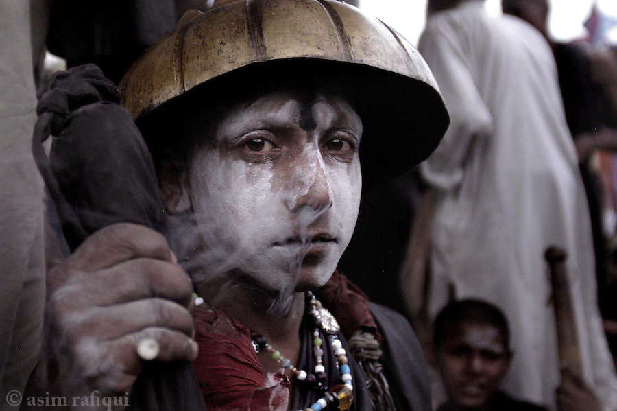 bari imam shrine, islamabad, pakistan 2004: a young member of a troupe of holy men getting high on marijuana before performaning a ritual dance at the bari imam's tombstone.  reminiscent of hindu sadhu tradition, such holy men are unique to shrines in the punjab<br />