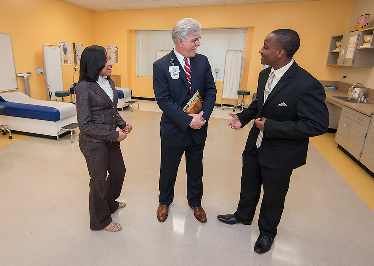 Memorial Hermann Chief Operating Officer Tom Flanagan, center, talks with students Brinajor Barrett, left, and Dominic Franklin, right, in the clinical classroom during the Hartman Middle School Health and Medical wing dedication, April 3, 2014.