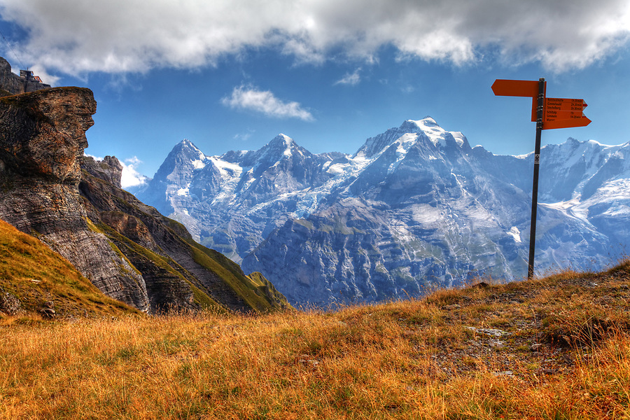 Trail markers in meadow on Schilthorn mountain, looking to Eiger, Mönch and Jungfrau in background, Switzerland