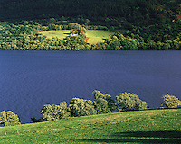 Sunlight picks out a distant cottage seen across Loch Tay in a green spring landscape, Perthshire, Scotlan