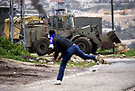 A Palestinian protester throws stones at Israeli bulldozer during a demonstration against the expropriation of Palestinian land by Israel in the village of Kfar Qaddum, near the West Bank city of Nablus, on March 2, 2012.  Photo by Wagdi Eshtayah