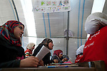 "Seventh-grade girls attend Arabic class at the school in Azaz Camp, just inside the Syrian border with Turkey, Feb. 26, 2013. A private charity donated the tents for the school, which has around 800 students between the ages of 6 and 16. Desks and other materials were salvaged from schools in Azaz village a few kilometers away. The school opened two months ago, and because there are so many children, they attend either a morning or an afternoon session, learning math, Arabic, English, and religion. Almost all of the teachers and staff are refugees and reside in the camp. The children come to school with special challenges--they may have psychological distress because of traumatic events or health problems due to poor living conditions in the camp, and some have not been in school for a long time and have to catch up to their grade level. ""We try everything to make them happy,"" said a teacher, Abdul Razaq. According to administrators, this camp holds roughly 9,000 to 10,000 internally displaced persons (IDP's). Two meals per day are provided by a Turkish humanitarian organization, and Qatar Red Crescent provided tents. There is very little electricity, and no running water. There is also a refugee camp on the Turkish side of the border, but it is full. The UN Refugee Agency has reported a sharp increase in refugees fleeing Syria for neighboring countries in the first months of 2013."