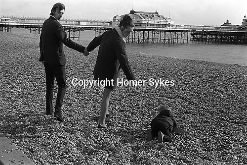 Family outing on Brighton beach. Sussex England 1970