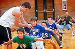 Players hold their defensive stance as Williamsport basketball sophomore Christopher Kinley, left, helps with the right stance during Little Millionaires basketball practice at the high school Tuesday Oct. 26, 2010.