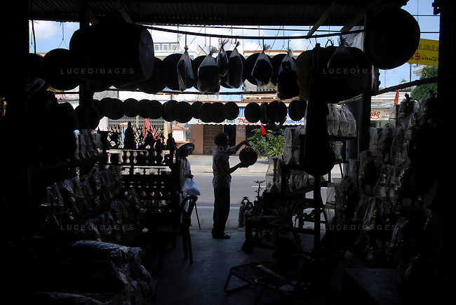 A shop owner hangs gongs, a popular souvenir among tourists, in Hoi An, Vietnam.