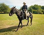 Old Bethpage, New York, USA. September 28, 2014. Rough Rider BERNADETTE MCHUGH, holds Elwood, her Jack Russel dog, while riding Noche the black Spanish Mustang, at the 172nd Long Island Fair, a six-day fall county fair held late September and early October. A yearly event since 1842, the old-time festival is now held at a reconstructed fairground at Old Bethpage Village Restoration.