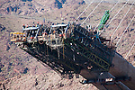 The new Boulder Canyon Bridge, Nevada, arches under construction.<br /> <br /> Arches and cables over the canyon will create one of the world's highest and longest concrete arch bridges for US 93 to aliveate traffic and security concerns of traffic crossing Hoover Dam.<br /> <br /> Construction tramway and basket with worker.