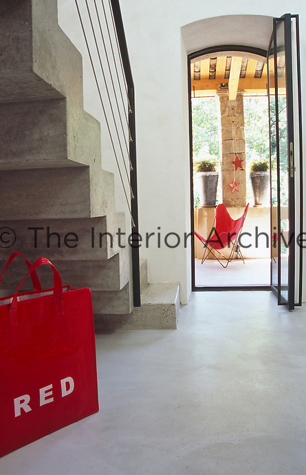 A red shopping bag sits below the concrete staircase with a view through to the terrace